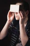 Les émotions d'une jeune fille regardant par le carton de Google image stock