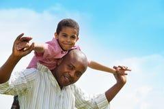 Les épaules de garçon du père noir d'équitation Images libres de droits