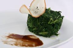 Les épinards cuits avec une tranche de pain grillé ont admirablement servi images libres de droits