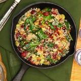 Les épinards et la canneberge de quinoa de vue supérieure font cuire au four dans la poêle de fonte Photo stock