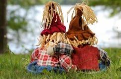 Les épouvantails de garçon et de fille soutiennent la vue se reposant par le lac Photographie stock