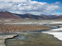 Les étangs et les courbures salent le lac de hautes montagnes, rivage blanc du sel, chaînes de montagne à l'arrière-plan, dans le Photographie stock libre de droits