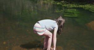 Les étapes de jeune fille dessus à une roche en rivière et se plie alors plus de pour éclabousser l'eau clips vidéos