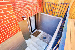 Les étapes extérieures mènent au sous-sol souterrain de la maison de brique Photo libre de droits