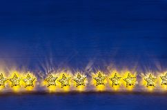 Les étoiles de jaune de lumières de Noël brûlent sur le fond en bois d'outre-mer foncé image stock