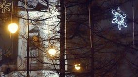Les étoiles de lueur de Noël accrochent sur la rue dans la soirée clips vidéos
