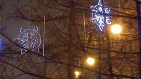 Les étoiles de lueur de Noël accrochent sur la rue dans la ville de soirée clips vidéos