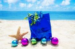 Les étoiles de mer avec des boules de Noël et le cadeau mettent en sac sur la plage Image libre de droits