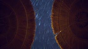 Les étoiles traîne les traces de voies sur un paysage bleu-foncé profond de fond de vue de ciel, parapluies de plage symétriques  clips vidéos