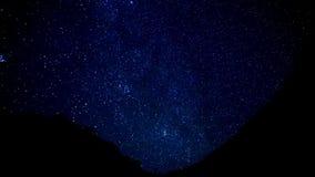 Les étoiles traînent la temps-faute dans le premier plan de la montagne de silhouette banque de vidéos