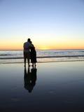 Les étreintes de coucher du soleil ont reflété II Image libre de droits