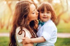 les étreintes de maman et l'enfant en bas âge heureux de baiser badinent le fils extérieur au printemps ou l'été Jour affectueux  Images stock