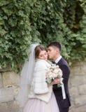 Les étreintes de marié offrent la jeune mariée dans le manteau de fourrure blanc sous le mur photographie stock