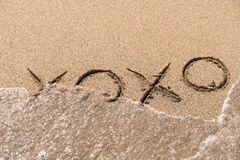 Les étreintes et les baisers XOXO se connectent le sable Images libres de droits