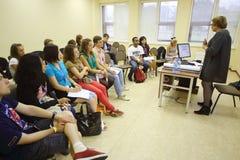 Les étudiants écoutent le conférencier à la voix globale de la jeunesse Images stock