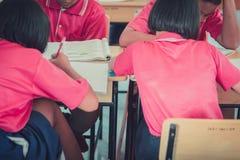 Les étudiants étudient dans la salle de classe d'école primaire Image libre de droits