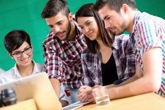 Les étudiants communiquent en café avec l'ordinateur portable Images stock