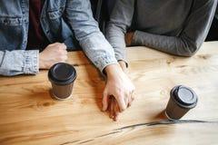 Les étudiants couplent prendre le déjeuner romatic jugeant à l'intérieur des mains en gros plan Images stock