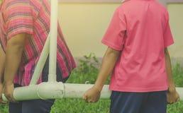 Les étudiants déplacent un but pendant une session s'exerçante du football dans le scho photos stock