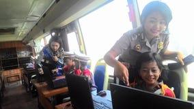 Les étudiants d'école se sont habillés dans la police apprenant l'autobus croisé de passages Photographie stock libre de droits