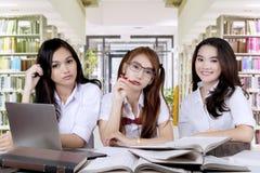 Les étudiants de lycée assez s'asseyent dans la bibliothèque Photo stock