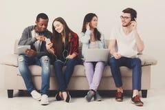 Les étudiants divers à l'aide des instruments, s'asseyent sur le sofa Photo stock