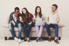 Les étudiants divers à l'aide des instruments, s'asseyent sur le sofa Photographie stock libre de droits