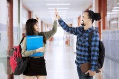Les étudiants donnent la haute cinq dans le couloir d'école Image stock