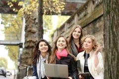 Les étudiants européens apprenant avec l'ordinateur portable et les papiers, se reposant sur soient Image stock