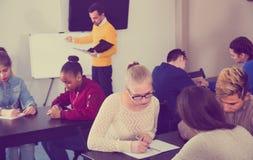 Les étudiants féminins et masculins travaillent dans de grands groupes images libres de droits