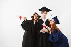 Les étudiants internationaux reçoit un diplôme la pose de sourire de réjouissance au-dessus du fond blanc photographie stock libre de droits