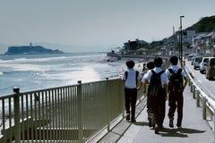 Les étudiants japonais marchent à la maison sur la plage image stock