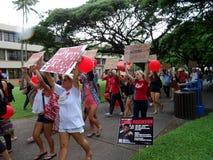 Les étudiants marchent par le campus protestant le coût de l'université image libre de droits