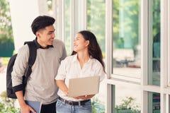 Les étudiants ou les collègues heureux de couples d'Asiatique utilisent l'ordinateur portable a images stock