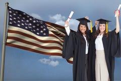 les étudiants portant une location de robe longue montrent le diplôme devant le drapeau américain sur le fond de ciel Photos libres de droits