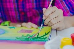 Les étudiants pratiquent peindre le paysage à l'aide des couleurs d'affiche Image stock