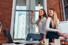 Les étudiants s'asseyant ensemble sur le bureau dans la salle de classe, une fille se dirigeant à l'ampoule aiment avoir une idée Photographie stock