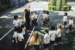 Les étudiants se tenant tenants des mains en cercle forment Photo libre de droits