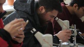 Les étudiants sur la formation pratique avec les microscopes optiques regardent dans des oculaires, essais de femme pour enlever  clips vidéos