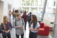 Les étudiants tenant les comprimés et le téléphone parlent dans le lobby d'université Photos stock