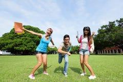 Les étudiants universitaires heureux sautent Photos stock