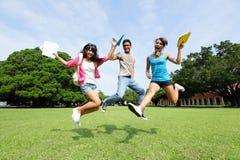 Les étudiants universitaires heureux sautent Image stock