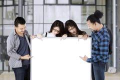 Les étudiants universitaires tiennent le tableau blanc vide Photographie stock