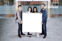 Les étudiants universitaires tiennent un conseil blanc avec l'espace de copie Photos libres de droits