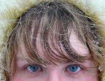 Les œil bleu et le cheveu de la femme sous la neige images libres de droits