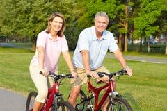 Les aînés accouplent faire du vélo Image libre de droits