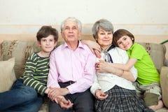 Les aînés avec des grandkids s'asseyent sur un sofa Photo stock