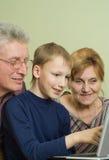 Les aînés avec son fils jouent dans un cahier Photo libre de droits