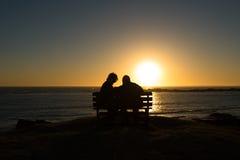 Les aînés couplent apprécier le coucher du soleil coloré photos stock