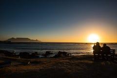 Les aînés couplent apprécier le coucher du soleil coloré sur la plage chez Bloubergstrand en Afrique du Sud, faisant face à la mo Photos stock